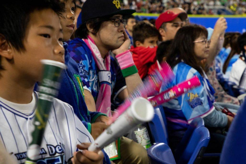 Fans clap together mini-baseball bats to cheer on their players and team.