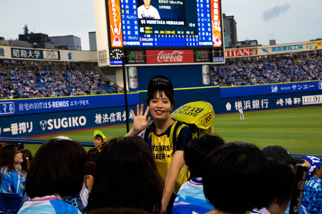 Young women carry a full keg of beer on their backs to sell to Japanese baseball fans. This girl is selling Baystars Beer, named after the team.