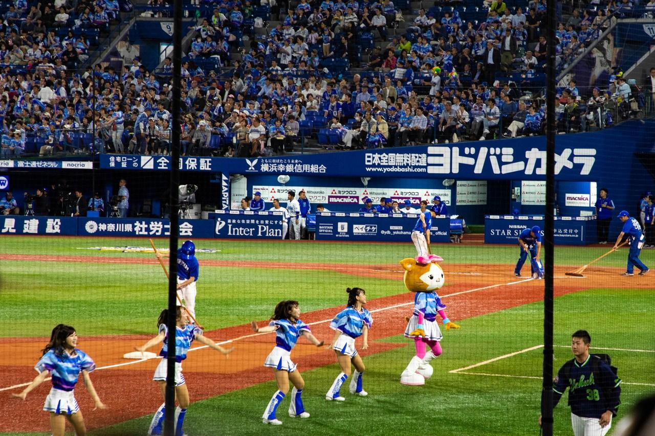 Yokohama Baystars Cheerleaders and mascot perform during half time.