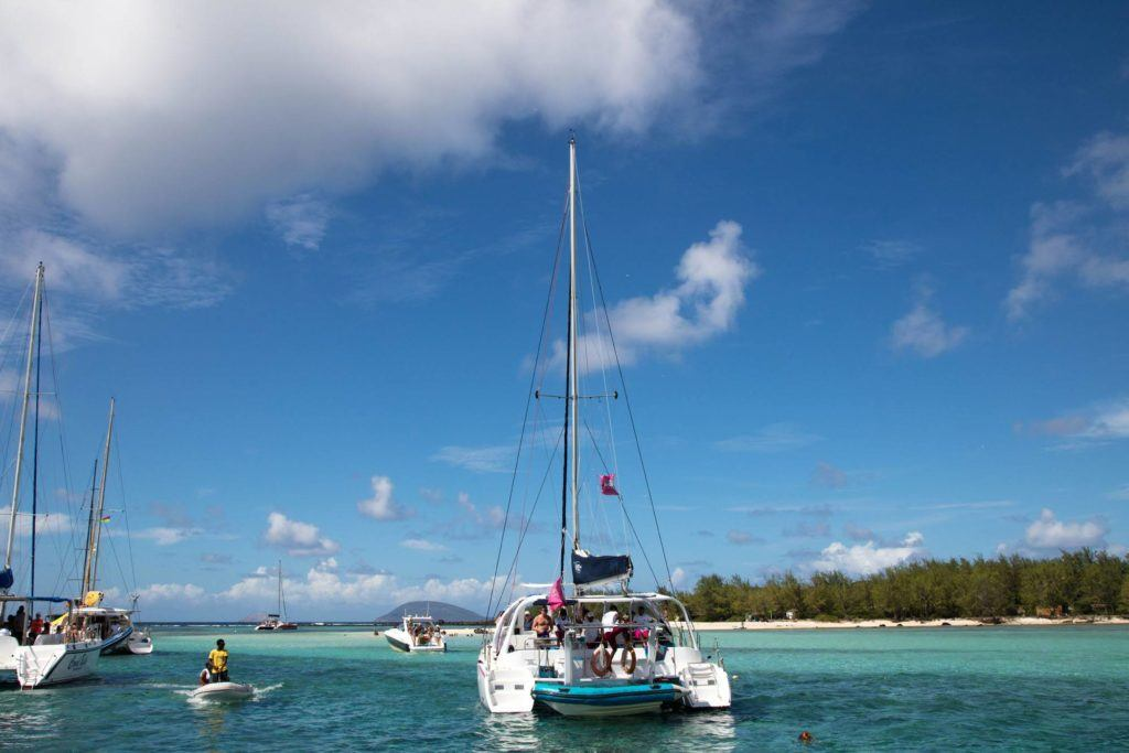 Catamaran and other boats parked near day trip island in Mauritius.