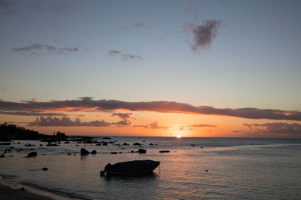 A silhouetted boat and rocks at sunset.