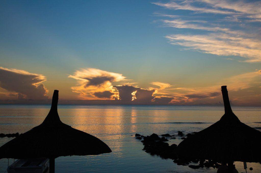 Sunset through the beach umbrellas of our resort.