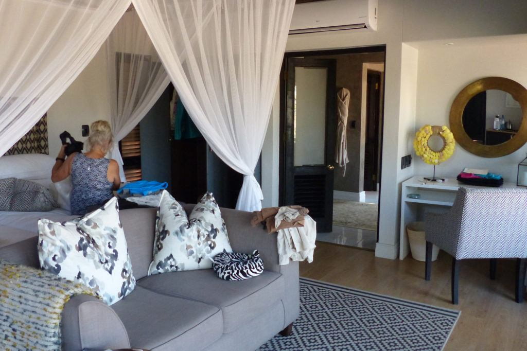 The interior of a Thornybush Game Lodge bungalow with mosquito-netted beds, a sitting area, and spacious bath.
