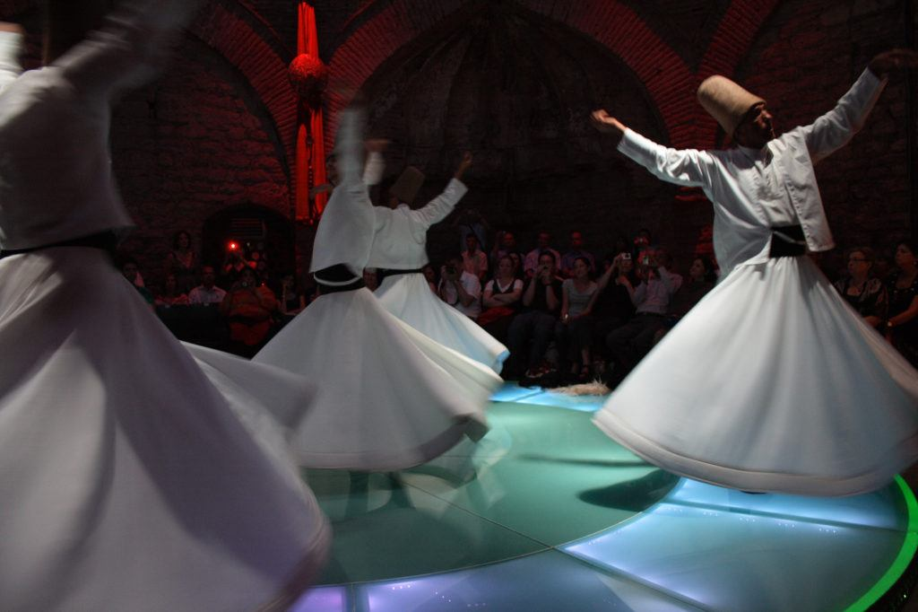 Whirling Dervishes twirl amid multi-colored lights.
