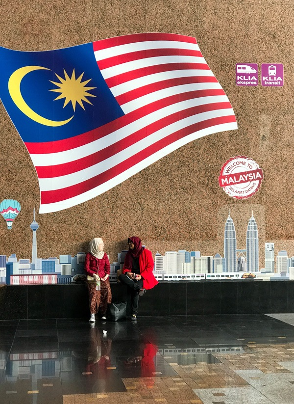 Two women sitting under Welcome to KL mural.