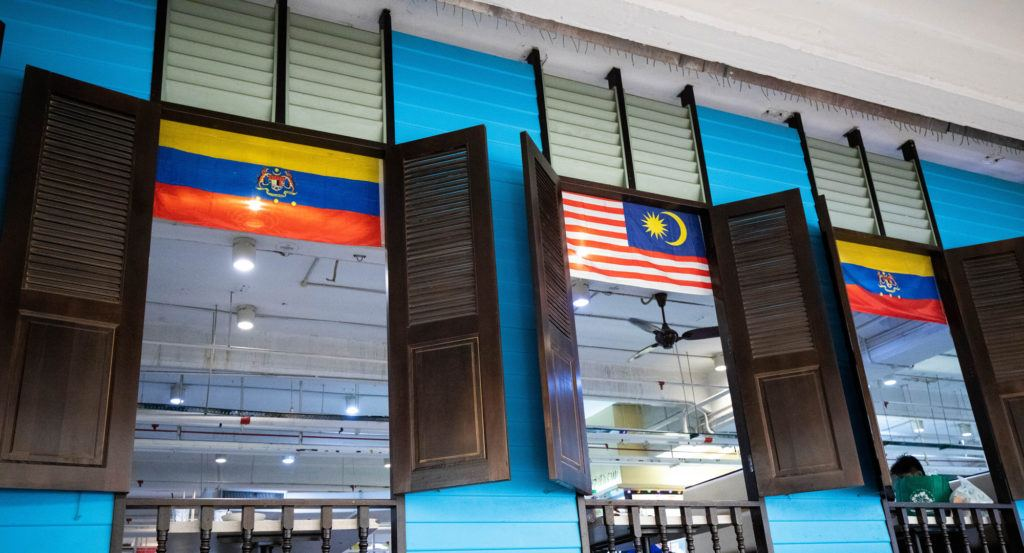 Interior of Central Market, windows of the food court on 2nd floor with Malaysian flags.