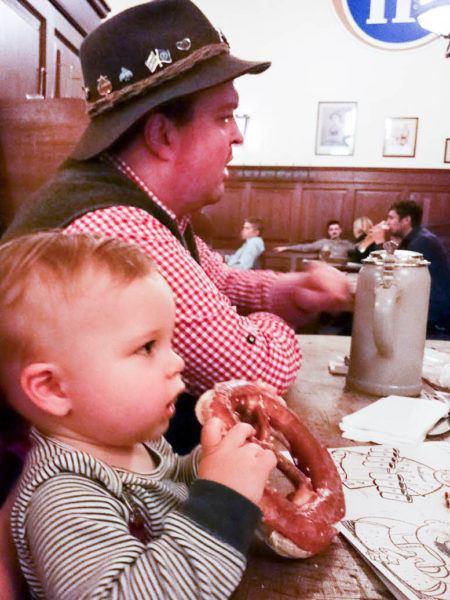 Little boy eating a pretzel.