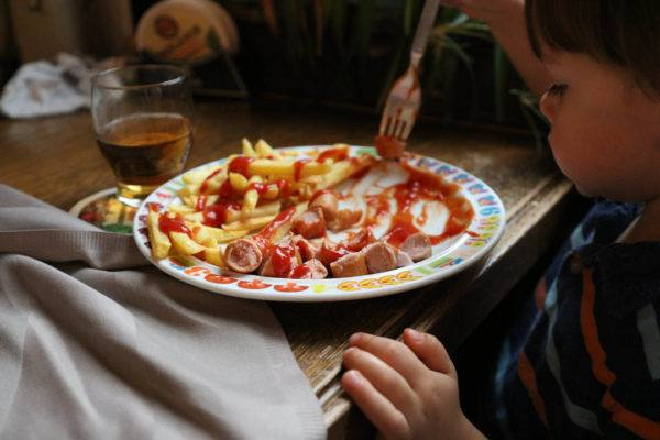 Little boy eating wurst and fries.