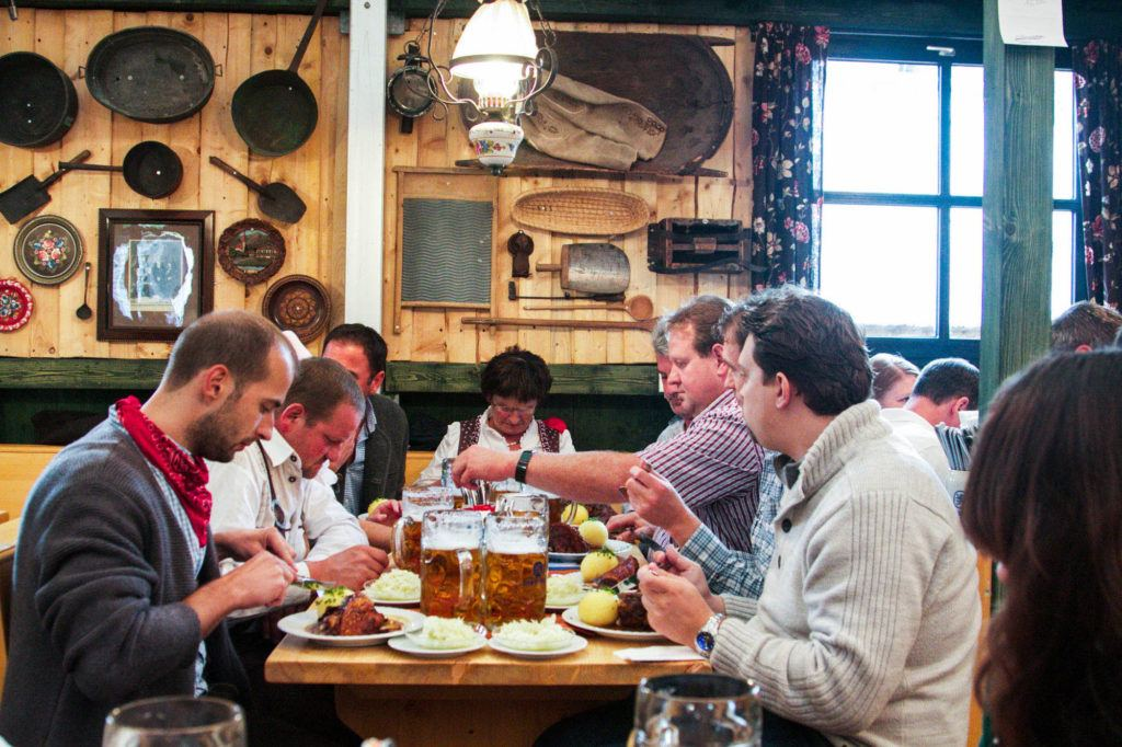 A group of people enjoying a meal in a typical German restaurant.