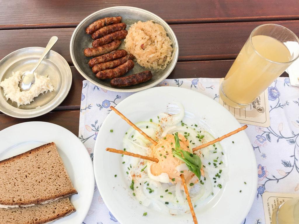 A Bavarian lunch of sausages, sauerkraut, Obatzda spread, and apple juice.