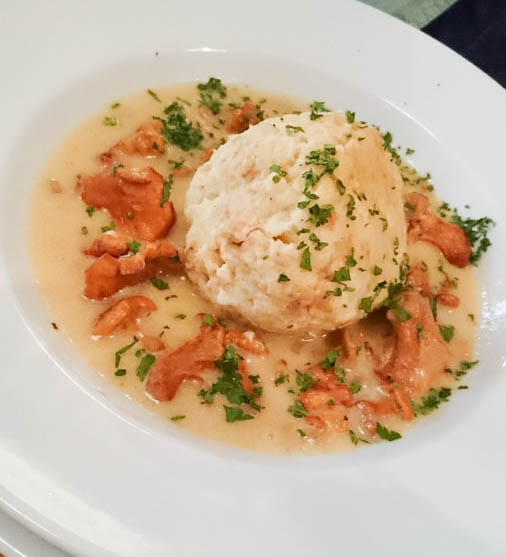 Vegetarian Dish of mushrooms and dumpling with sauce.