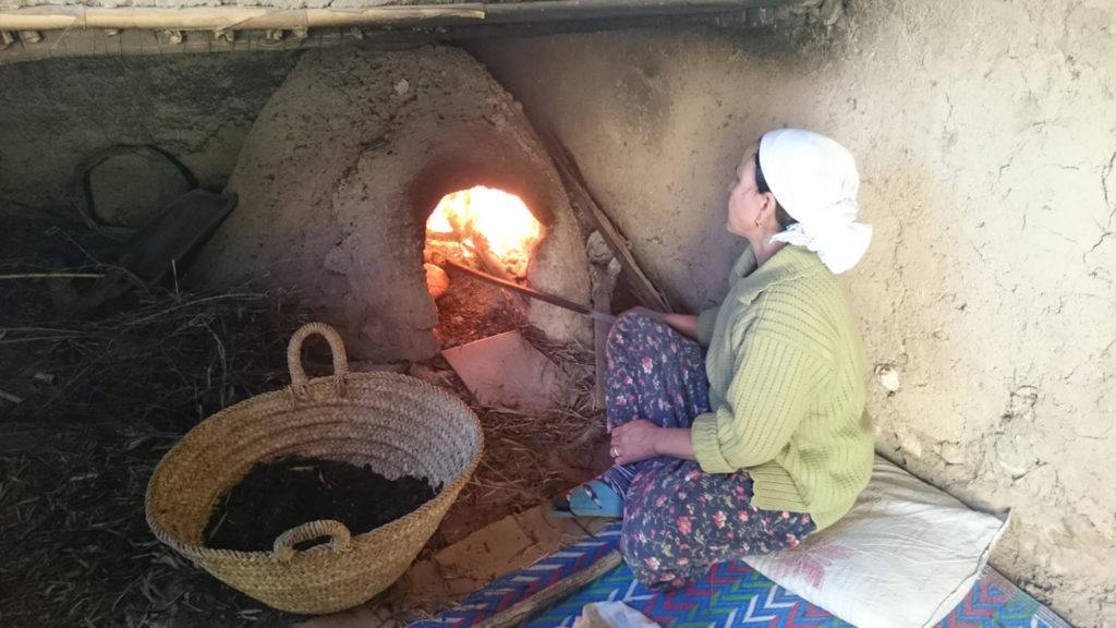 A woman tends bread in a traditional clay oven at the Berber Cultural Center in Marrakesh, Morocco.