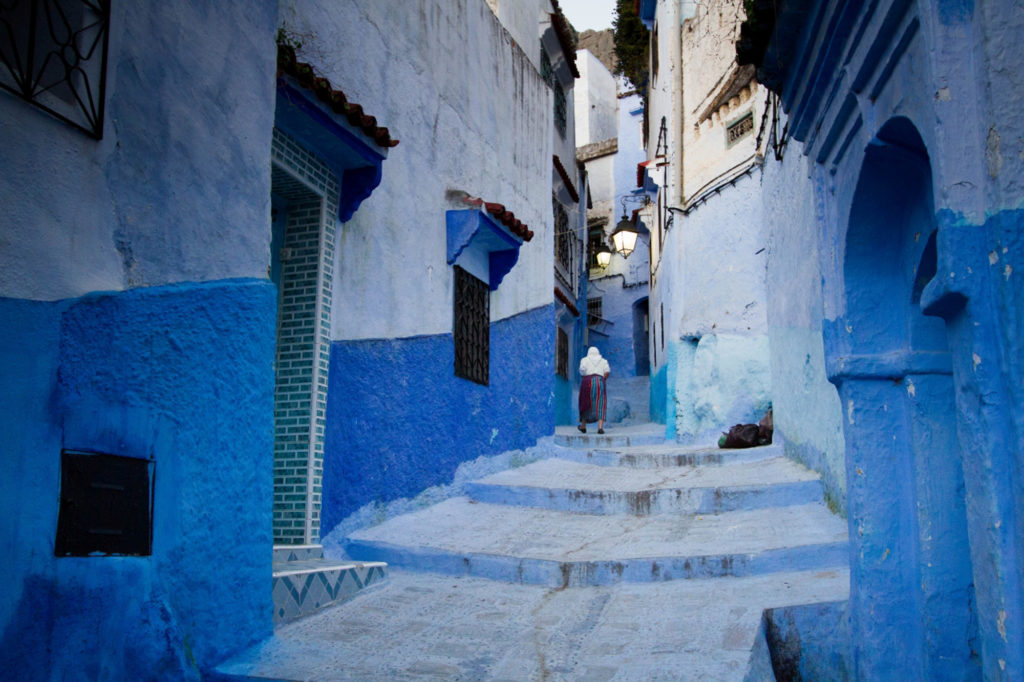 A woman walks through a narrow passage between the stunning blue-washed buildings in Chefchaouen, Morocco.