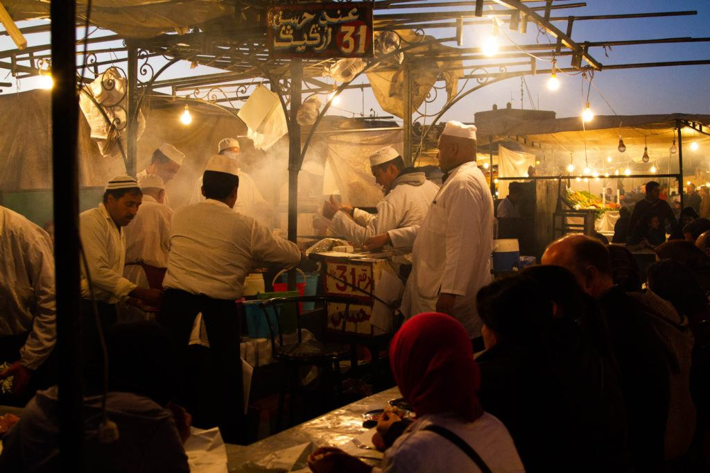 Food stall cooks work over steaming pots and grills to make Moroccan street food for crowds of people in Jemaa el Fna.