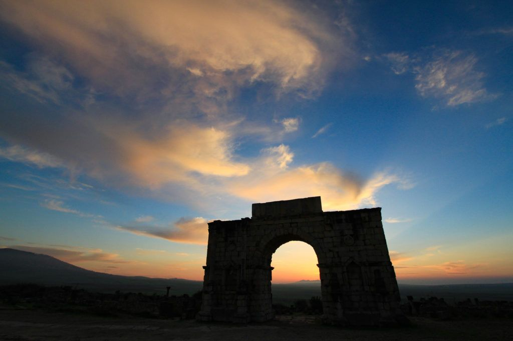 The sun is setting behind the Arch of Caracalla in the Roman ruins in Volubilis World Heritage Site, Morocco.