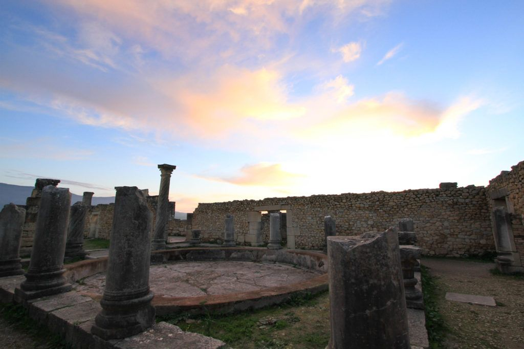 When visiting Volubilis, Morocco, plan to stay until dusk to experience the Roman ruins as the sun sets.