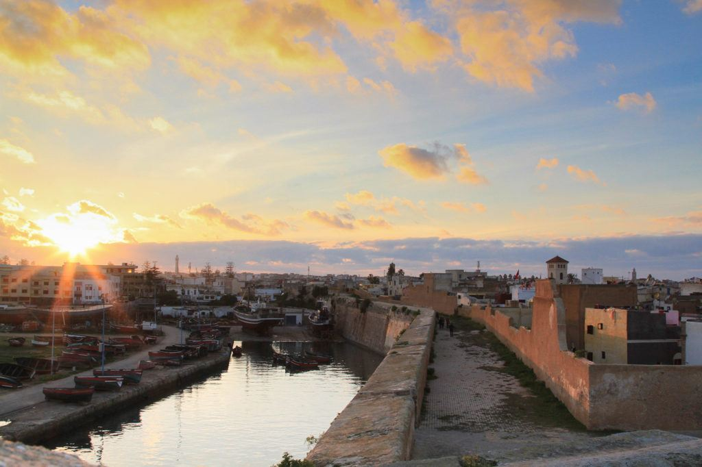 The sun sets behind the stone walls and canal in El Jadida, Morocco.