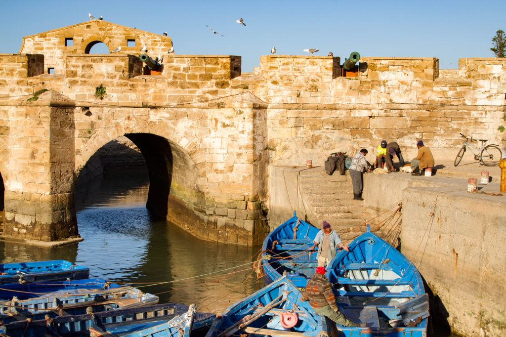 A group of fisherman on the fortress wall preparing their gear and loading their blue boats.