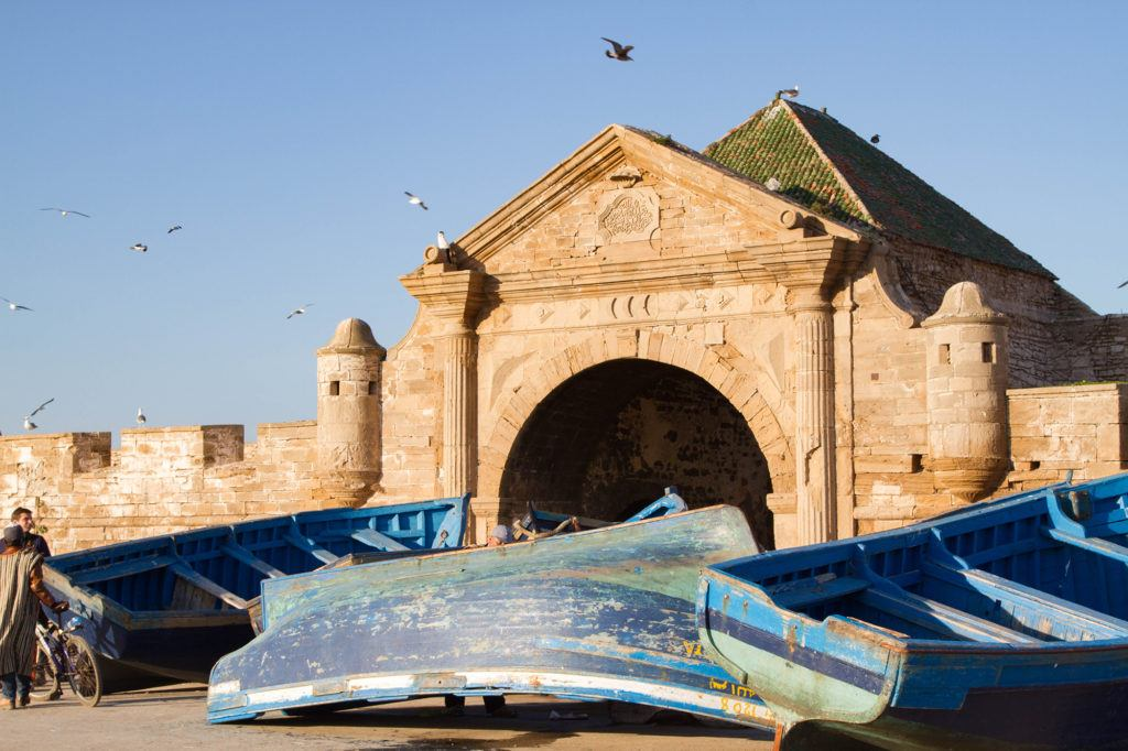 Blue fishing boats in front of Bab El Marsa, the gateway to Mogador Fortress in Essaouira.