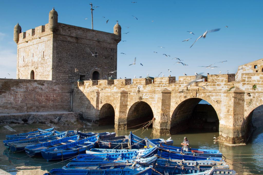Blue fishing boats tied together next to the fortress wall in Skala Port are an iconic sight to see in Essaouira.