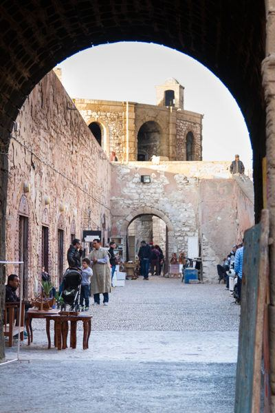 Looking through an arch into a passageway in the Essaouira city wall where men and a young boy appear to be shopping.