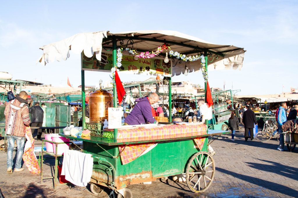 A green food cart is setup and ready to serve tea and sweets in Jemaa el Fna, the main square in Marrakesh.