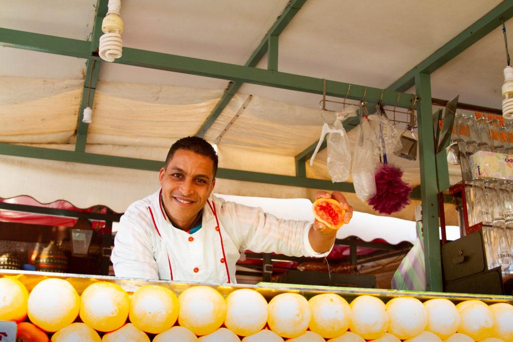 A Jemaa el Fna food stall vendor holds up half a grapefruit to show the freshness of his fresh-squeezed juice.