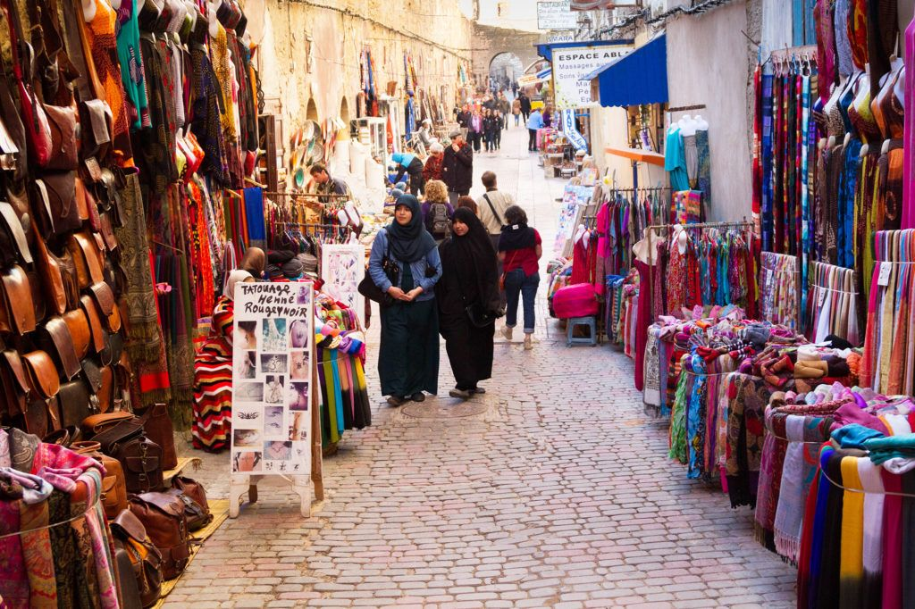 Women shopping at the stalls filled with brightly colored clothing and textiles in Le-Souk, in the Essaouira Medina.