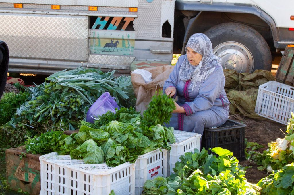 A women trims lettuce, herbs, and other vegetables at a Berber Market.