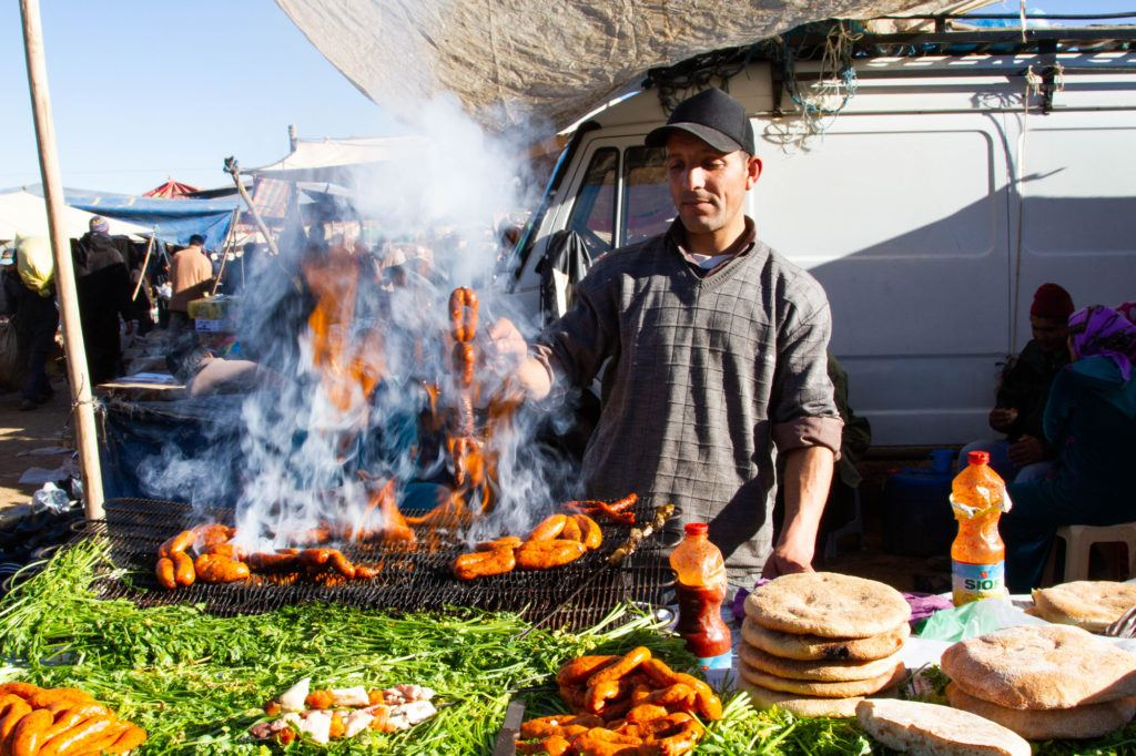 A Berber Market vendor grilling lamb merguez sausages.