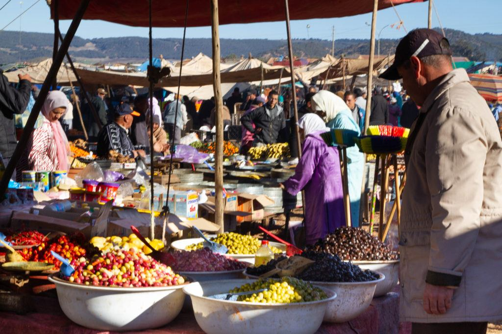 Stall at the Berber market with huge bowls heaped with different types and colors of olives.