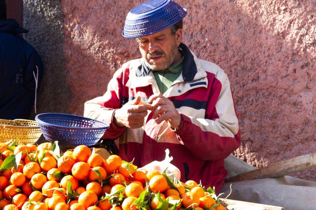 An orange vendor, wearing a blue plastic basket for a hat, sells fresh oranges from a cart in Jemaa el Fna.