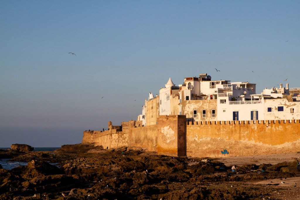 A golden glow highlights the walls and white stucco houses of Essaouira.