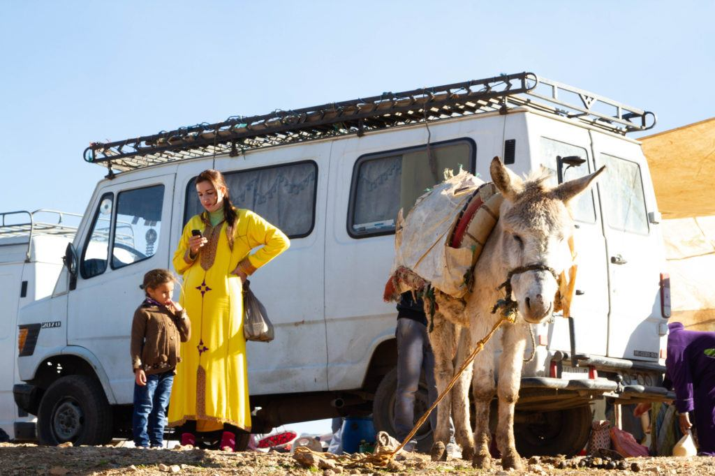 A young woman wearing a bright yellow djellaba is standing near a donkey and looking at her cell phone.