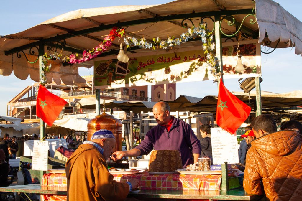 A vendor with his cart decorated with garland and Moroccan flags serves mint tea to a customer.