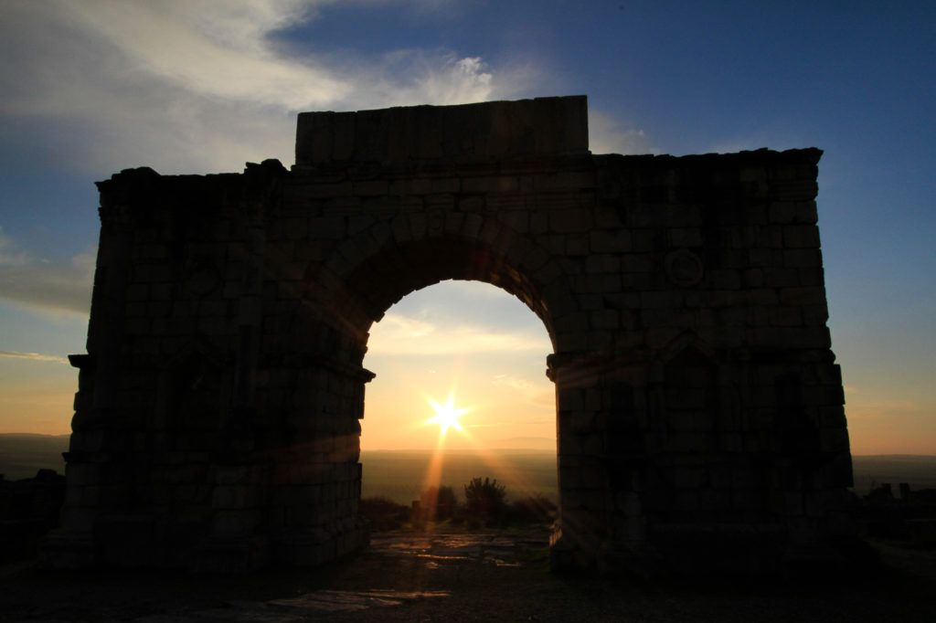 Setting sun shining through the triumphal Caracalla arch at the ruins in Volubilis, Morocco, A UNESCO World Heritage Site.
