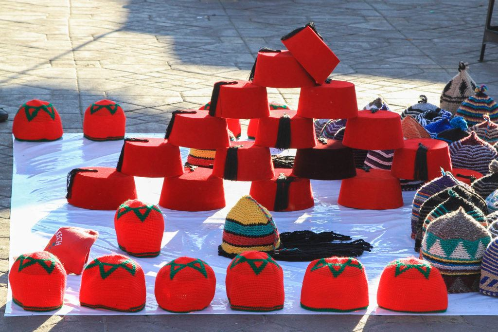 A vendor sells traditional red fez hats in the Jemaa el Fna market.