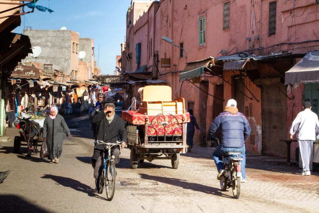 A busy Marrakech street scene with donkeys pulling carts, men on bikes, and a women carrying a shopping bag.