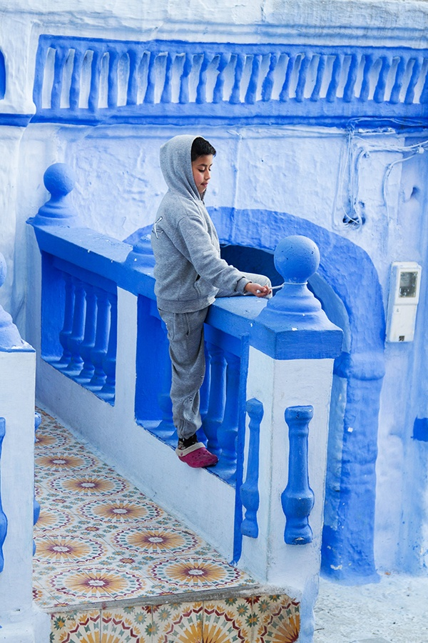 A little boy plays on a balcony banister in the midst of the blue city of Chefchaouen.