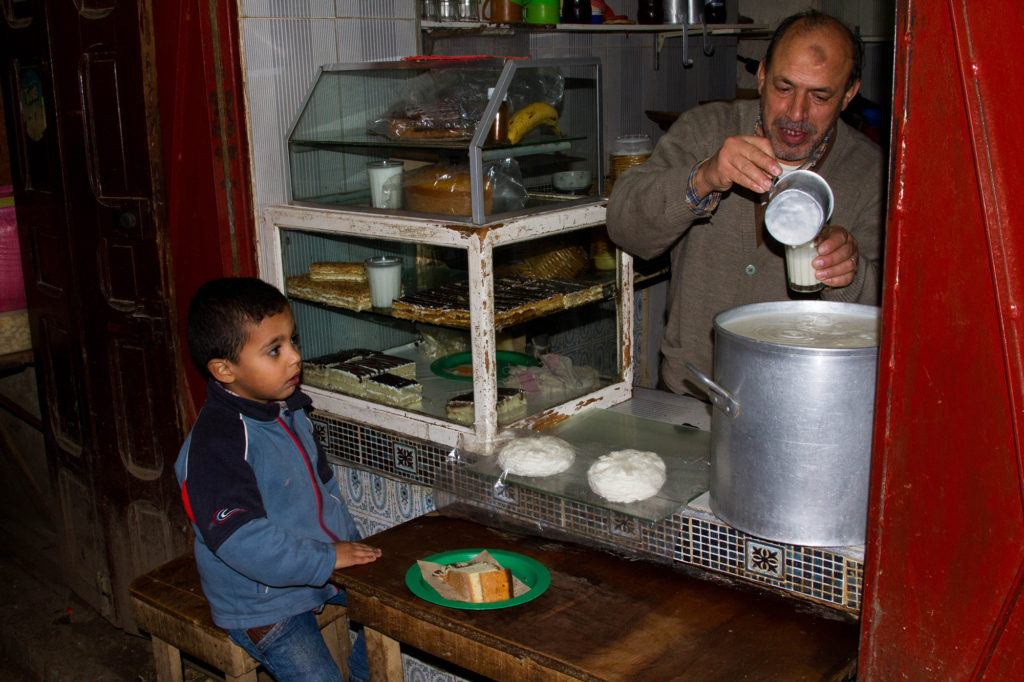 A young boy is served a snack at a small shop in the Fez Medina.