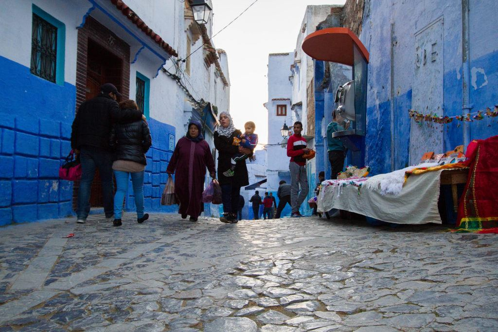 Late afternoon shoppers walking through the Old Town of Chefchaouen.