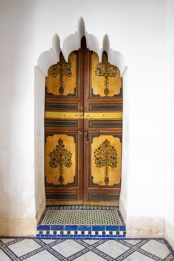 A door with painted panels inside an intricately shaped archway in Marrakech.