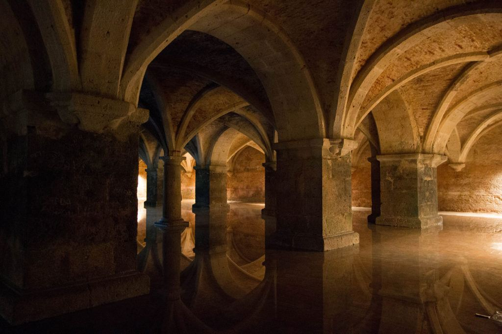 Underground cistern with stone pillars, rippling light, and sounds of dripping water.