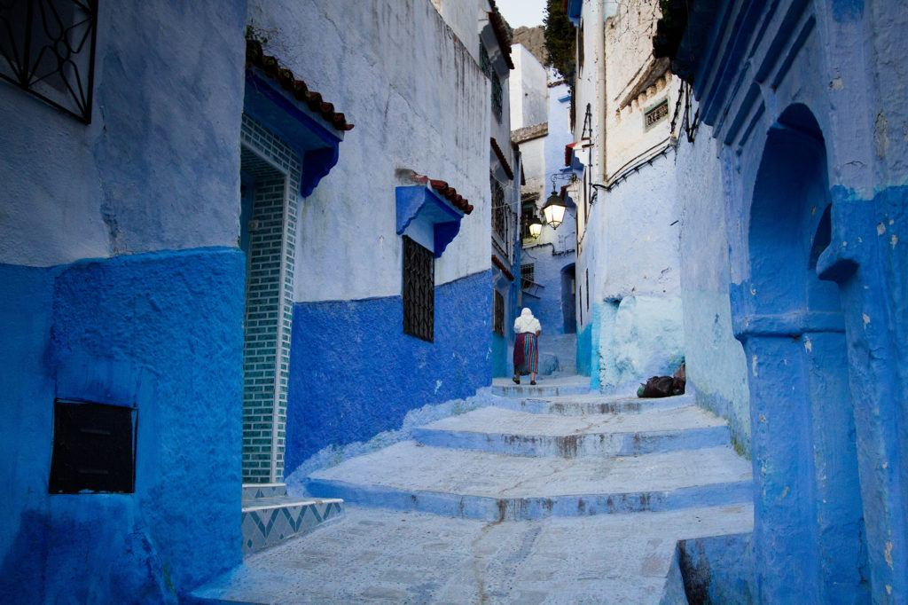A woman walks up some of the many blue steps.