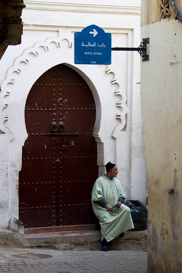 A man in traditional clothing waits at an intricately carved door.