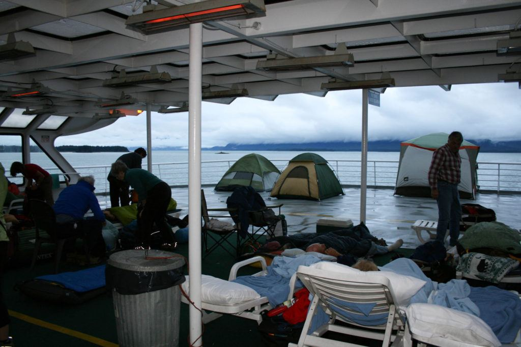 People sleeping on lounge chairs or in tents on the deck of the MV Columbia.
