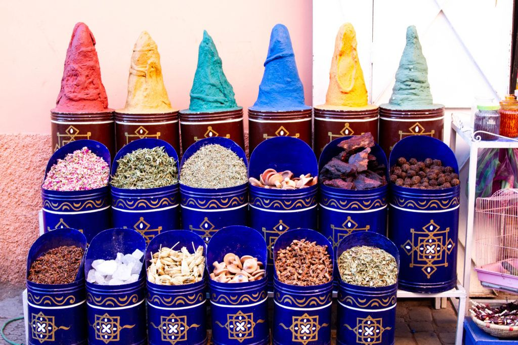 Spices and dried foods displayed in canisters in a Marrakech shop.