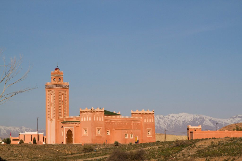 A very new looking reddish-pink mosque in a local village with the snow-capped High Atlas Mountains in the background.