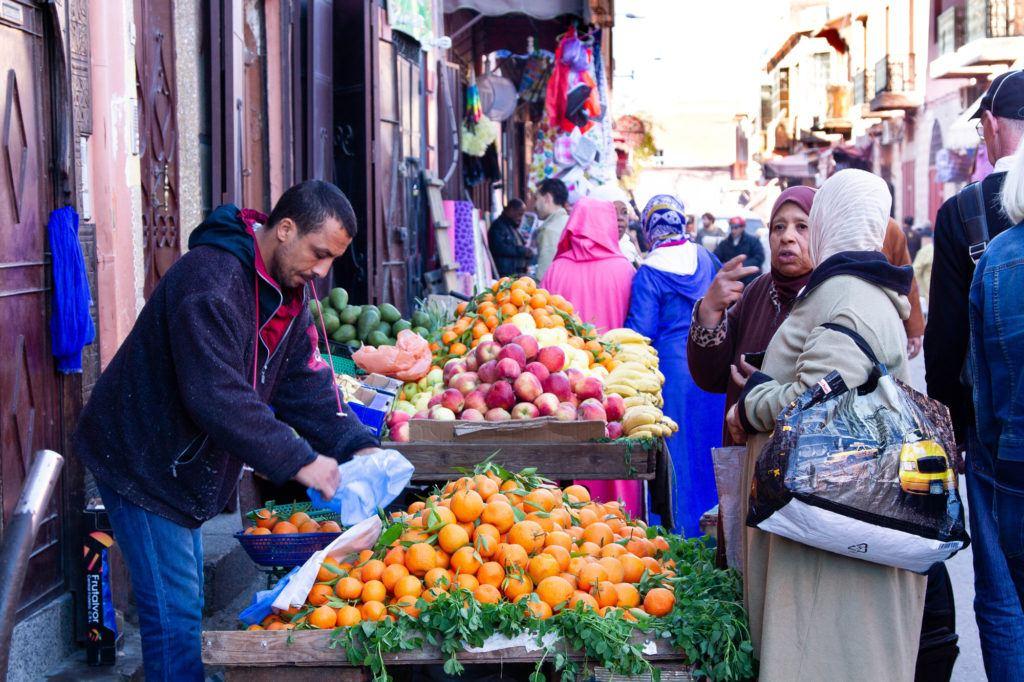 Women buying oranges from a fruit vendor in Marrakesh.