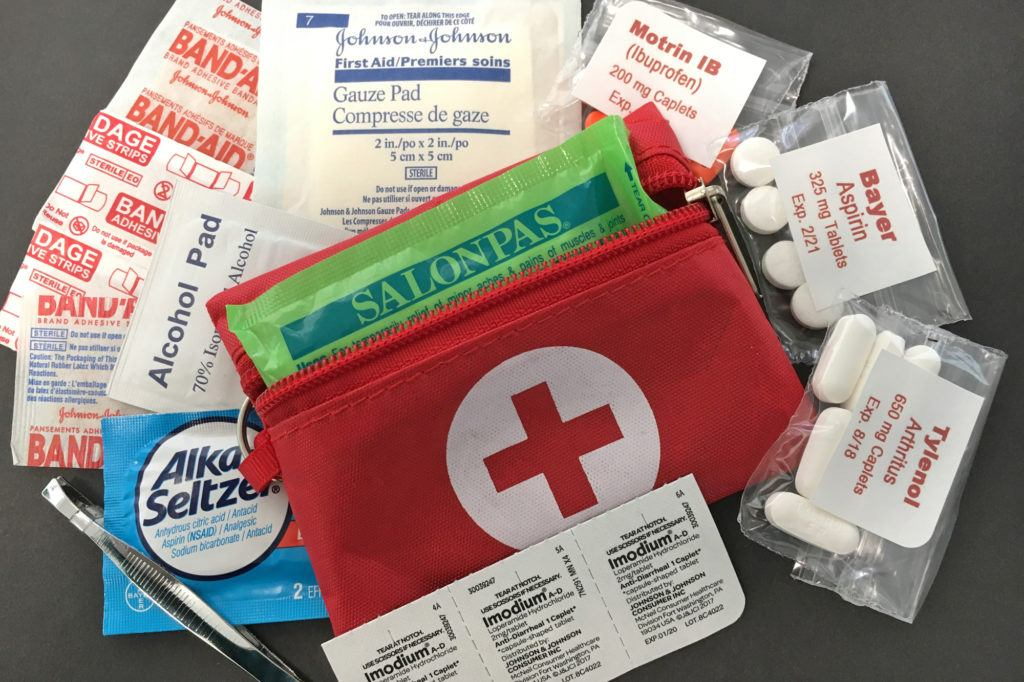 A tiny 3 x 4 inch first aid kit with basics like aspirin, alka seltzer, alcohol pads, tweezers, and assorted band aids.